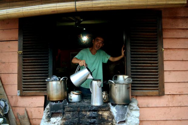 engkoh penjual yang asyik memasak kopinya