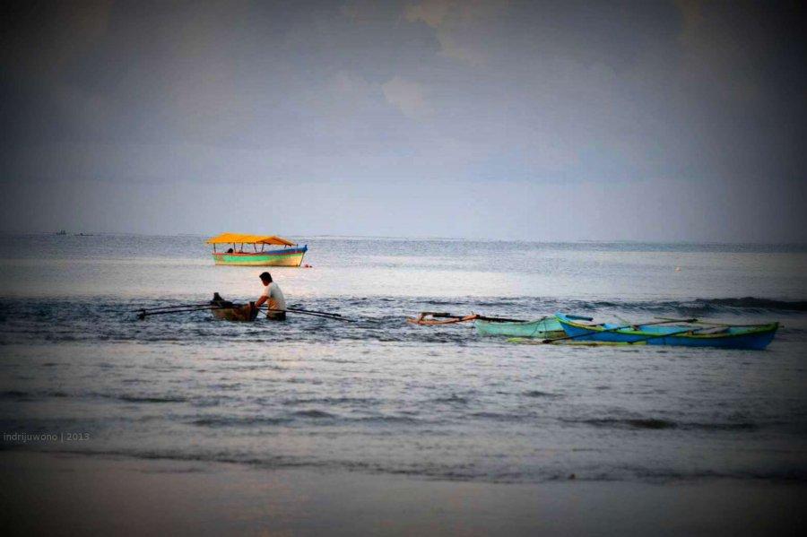 mendorong perahu ke tengah laut