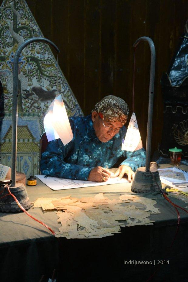 bapak yang sedang menggambar wayang
