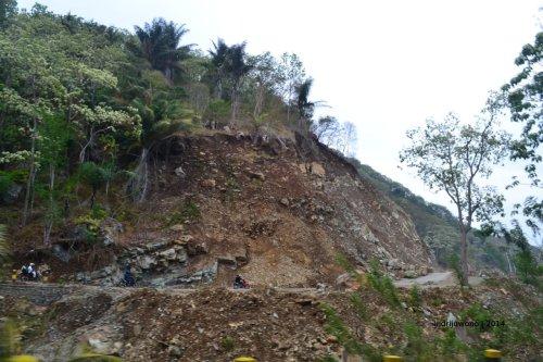 jalan dengan tebing batu yang bisa longsor ketika hujan