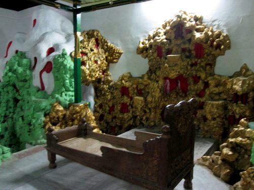 dipan jenazah dengan backdrop batu karang berlapis warna emas