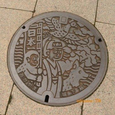 manhole cover di OKAYAMA, dengan legenda Momotaro