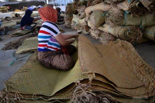 seorang pekerja yang menjahit tikar dengan tali rami supaya lebih lebar